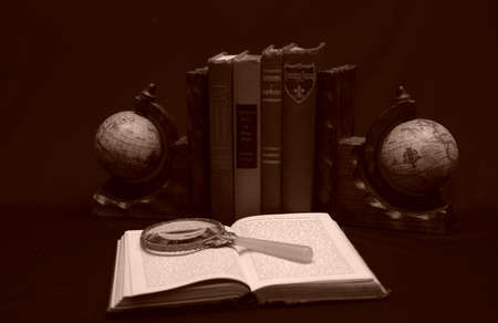 Photo of books with magnifying glass and candle Imagens