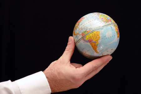 Man holding world globe with his fingertips.