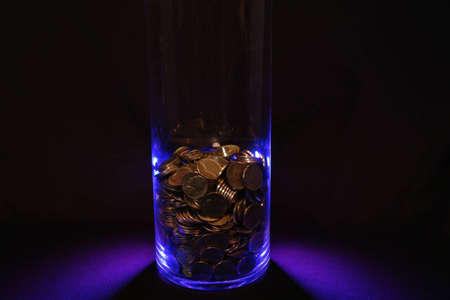 Jar of coins in blue on black.