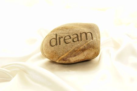a rock with the word dream inscribed in it against a soft white satin background. Imagens