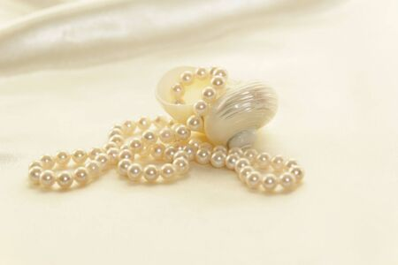 Beautiful white lustrous pearls against a soft white satin background.