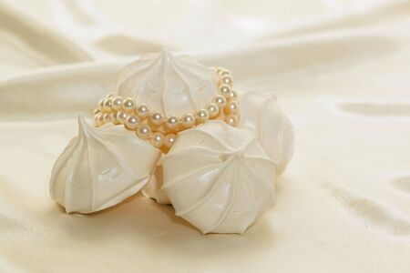 airy: White airy meringue cookies against a white satin background Stock Photo
