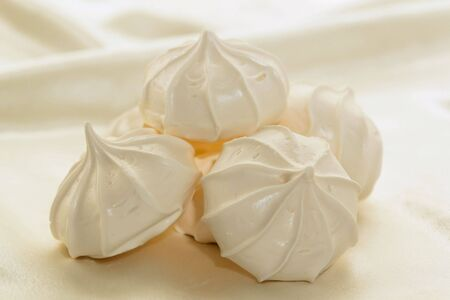 White airy meringue cookies against a white satin background Imagens