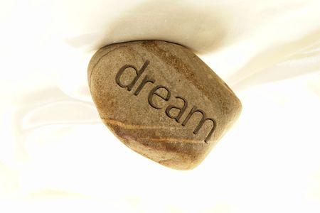inscribed: a rock with the word dream inscribed in it against a soft white satin background. Stock Photo