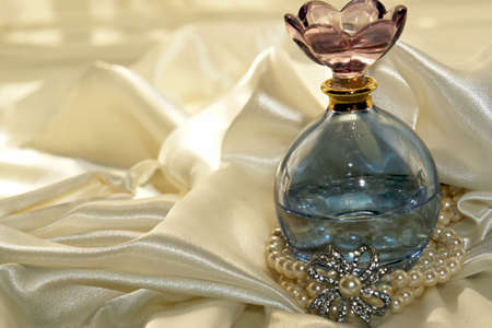 Blue tinted perfume bottle with pearls and diamonds on a soft white satin background Stock Photo