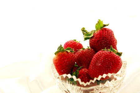 Scrumptuous red strawberries in a crystal bowl against a white satin background Banco de Imagens