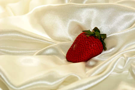 Single strawberry on a cloud of soft white satin