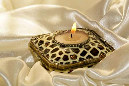 glistening: la quema de vela rodeado de suaves pliegues de la brillante satinado