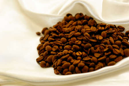 fresh roasted coffee beans on satin fabric