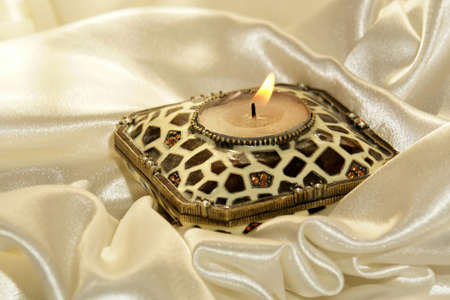 burning candle surrounded by soft folds of glistening satin