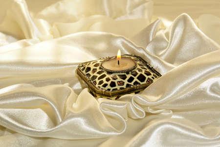 glistening: vela encendida, rodeado por suaves pliegues de la brillante satinado