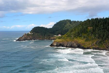 rich beautiful scenic view of the oregon coast with waves crashing and lighthouse off in the distance