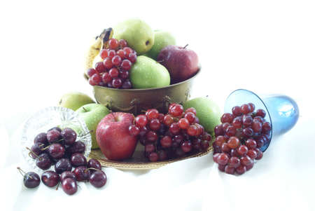 Overflowing brass fruit bowl with crystal bowl of cherries and goblet full of grapes.
