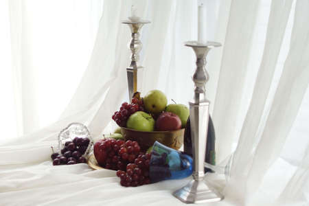 Silver candlesticks and overflowing brass fruit bowl with crystal and goblets.