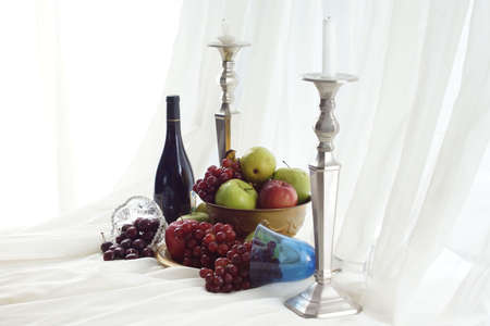 Candlesticks, red wine and brass fruit bowl overflowing onto table Imagens