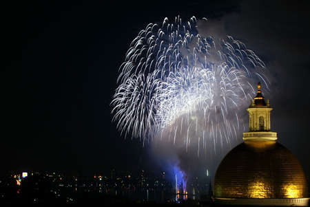 fourth of july fireworks explode in the sky over the charles river with the massachusetts state  in the foreground 写真素材