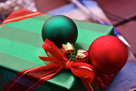 beautifully wrapped: beautifully wrapped and well adorned christmas present with ornaments and red bow with pen and notebook in background Stock Photo