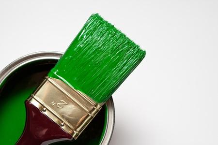 pinceau vert vif sur un pot de peinture