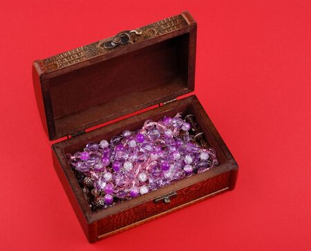 wooden casket with jewelry on red background.