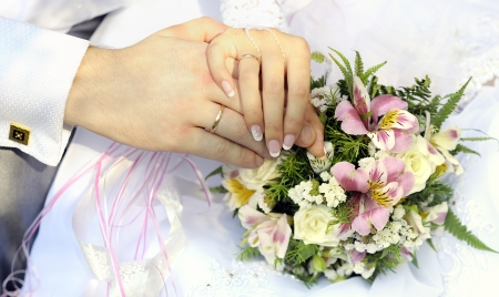 marriage ceremonies: Just married couple hands with flowers bouquet.