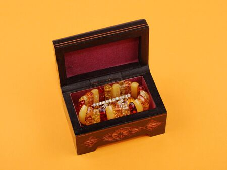 wooden casket with jewelry on yellow background.