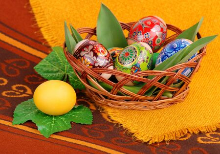 Colorful painted easter eggs in brown basket. photo