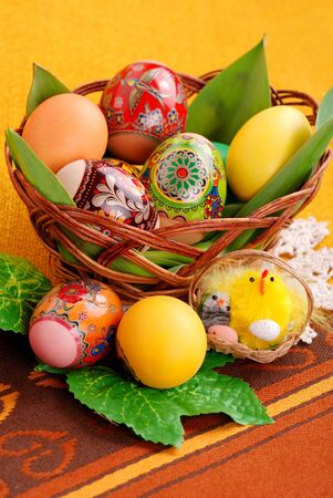 spring time: Colorful painted easter eggs in brown basket. Stock Photo
