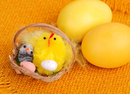 Yellow easter eggs with decorative chickens in basket. Stock Photo