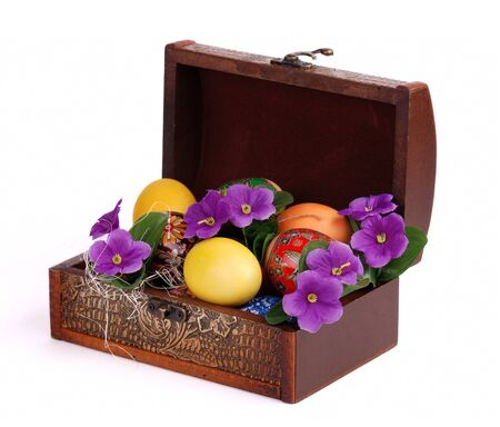 Colorful painted Easter Eggs in box with flowers isolated on white.