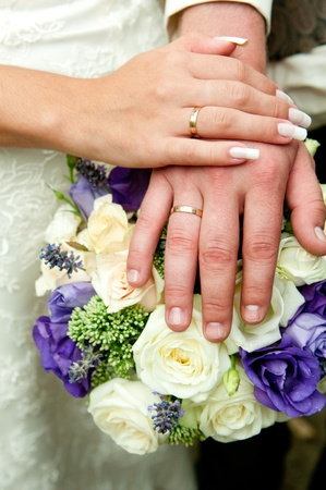 Just married couple hands with flowers bouquet.