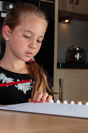 one room school house: Young girl thinking while doing homework at the kitchen table holding pencil