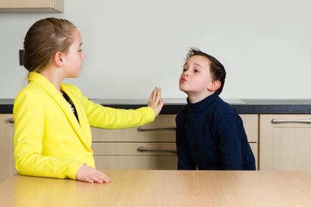예쁜 소녀가 키스를하려고하는 귀여운 어린 소년을 거절합니다. 스톡 콘텐츠