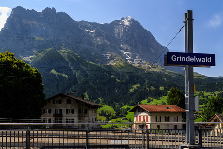Grindelwald nameplate in the railway station, the Eiger in the background in summer on a sunny day. Grindelwald, Bernese Oberland, Switzerland
