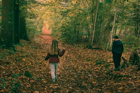 Boy and girl walking in a forest in autumn 스톡 콘텐츠