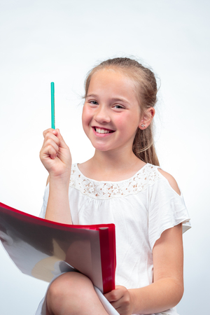 A cute 10-year-old caucasian schoolgirl smiling while holding up a pencil in the air and her note pad on her knee against a light background