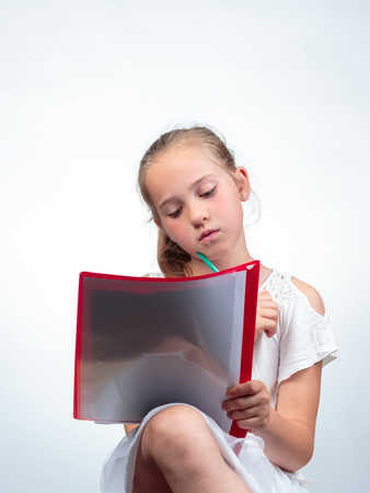Cute 10-year-old caucasian schoolgirl looking at or reading in an note pad while holding a pencil against her chin. Against a light background