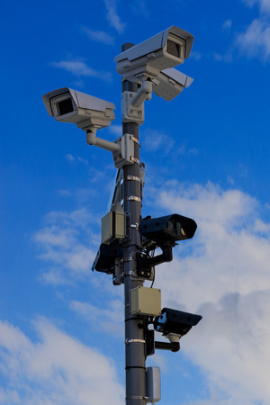 Different types of CCTV security cameras fixed on a pole on a blue sky background - security, big brother concept