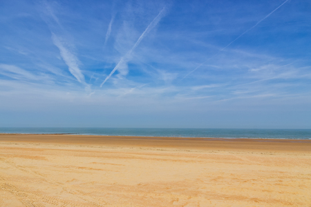 An empty beach with gold colored sand under a blue sky with some clouds on a sunny bright day. Ostend, Belgium, Europe