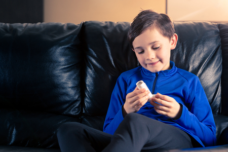 8 year old boy wearing sportive clothing holding an asthma inhaler sitting in sofa. Concepts : health, illness, doping Foto de archivo