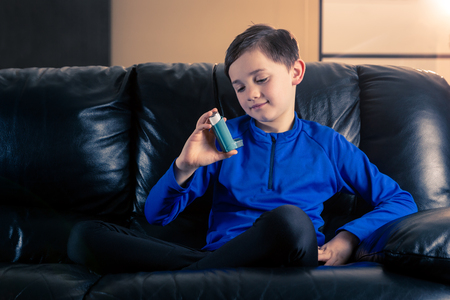 8 year old boy wearing sportive clothing looking at his asthma inhaler sitting in sofa. Concepts : health, illness, doping Foto de archivo