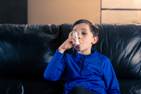 8 year old boy wearing sportive clothing using an asthma inhaler sitting in sofa. Concepts : health, illness, doping