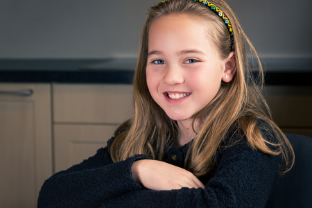 Portrait of beautiful smiling 10 year old caucasian girl, sitting at home, looking at camera 写真素材