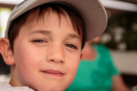Portrait of a cute little 8 year old boy outdoors wearing a gray baseball hat looking in the camera Stock Photo
