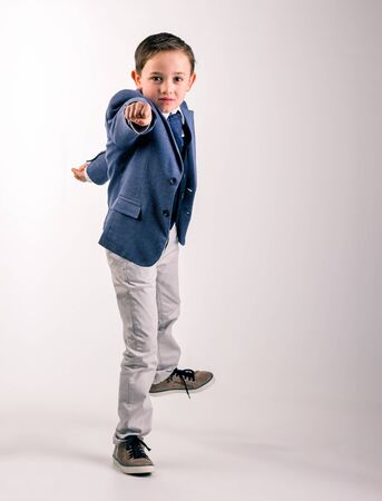 Studio shot of 8 year old boy, dressed up in suit, raising up his fist forward showing energy and determination Banco de Imagens