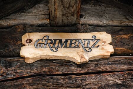 Wooden artisan nameplate of Grimentz hanging on aged wood boards in a chalet or log cabin. Grimentz, Val d' Anniviers, Valais, Switzerland