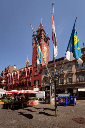 Basel, Switzerland - JULY 31 2018: City market on the Marktplatz in front of the historic red facade city hall with some flags in the foreground