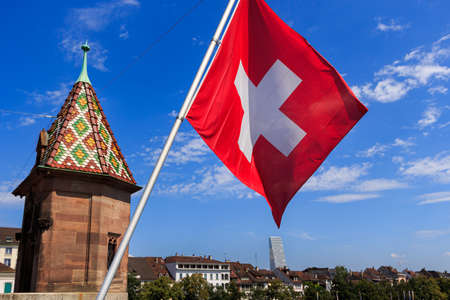 Swiss flag on a bridge in Basel (Switzerland), tower and city skyline against bright blue sky 免版税图像