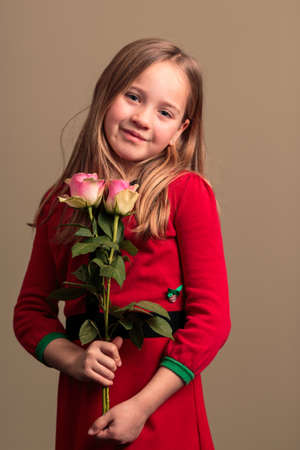 Young pretty 8 year old girl wearing a red dress holding flowers isolated on orange colored background