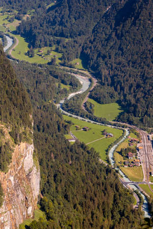 High angle view from Hunnenflue on the curvy run of the Lütschine river between green alpine pastures near Zweilütschinen. Jungfrau region, Bernese Oberland, Switzerland
