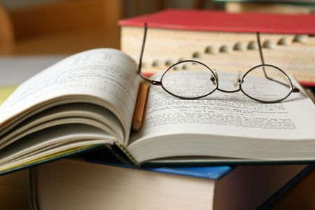 Text books on table with glasses and pencil Stock Photo